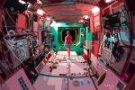 1girl anhdang blue_shorts brown_hair cable commentary english_commentary facing_away fisheye from_behind hair_bun indoors machinery original red_shirt scenery shirt short_sleeves shorts signature solo space space_station