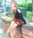 1girl abigail_williams_(fate/grand_order) alternate_costume arm_cutout bangs bare_shoulders black_shirt blonde_hair blush casual clothing_cutout commentary_request contemporary fate/grand_order fate_(series) feet_out_of_frame light_rays long_hair long_sleeves looking_at_viewer miniskirt open_mouth outdoors parted_bangs pleated_skirt red_skirt sakazakinchan shirt shoulder_cutout sitting skirt solo sunbeam sunlight thigh_strap tree