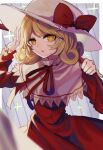 1girl blonde_hair blurry blurry_foreground border bright_pupils capelet commentary_request cowboy_shot curly_hair depth_of_field dress elly_(touhou) hand_up hat hat_ribbon highres holding holding_scythe ishikawa_sparerib juliet_sleeves long_sleeves looking_at_viewer medium_hair neck_ribbon outside_border parted_lips puffy_sleeves red_dress red_neckwear red_ribbon ribbon scythe solo standing touhou touhou_(pc-98) white_border white_headwear yellow_eyes