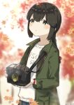 1girl autumn_leaves black_eyes black_hair braid camera clothes_writing commentary_request green_jacket hair_between_eyes holding holding_camera isonami_(kantai_collection) jacket kantai_collection low_twintails official_alternate_costume sidelocks solo twin_braids twintails upper_body yamashichi_(mtseven)