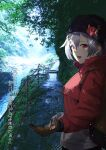 1girl backpack bag black_headwear brown_gloves casual coat commentary_request down_jacket fate/grand_order fate_(series) forest gloves hair_between_eyes highres jacket knit_hat looking_at_viewer nature outdoors railing red_eyes red_jacket river silver_hair solo tomoe_gozen_(fate/grand_order) tree vegetablenabe winter_clothes winter_coat winter_gloves