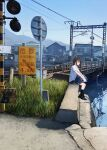 1girl bag black_hair black_legwear bridge day grass highres house kneehighs loafers original outdoors railroad_tracks sakeharasu scenery school_bag school_uniform shoes sitting sky solo water