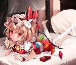 1girl ascot blonde_hair blush flandre_scarlet food hat hat_ribbon highres looking_at_viewer lying mob_cap mouth_hold on_bed on_stomach pantyhose pillow pocky puffy_short_sleeves puffy_sleeves red_eyes red_skirt red_vest ribbon shirt short_sleeves skirt solo touhou vest white_headwear white_legwear white_shirt wings wrist_cuffs yellow_neckwear zerocat