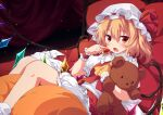 1girl bangs blonde_hair bloomers blush bow collared_shirt commentary_request crystal eyebrows_visible_through_hair fang feet_out_of_frame flandre_scarlet food frilled_shirt_collar frilled_skirt frills fruit hair_between_eyes hat hat_bow holding holding_food holding_fruit lying mob_cap object_hug on_back one_side_up open_mouth red_bow red_eyes red_skirt red_vest shirt skirt socks solo strawberry stuffed_animal stuffed_toy teddy_bear touhou ugume underwear vest white_bloomers white_headwear white_legwear white_shirt wings