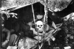 1girl 3boys bags_under_eyes bangs bitchcraft123 body_writing breasts breath greyscale gun holding holding_gun holding_weapon intrepid_(kancolle) kantai_collection large_breasts monochrome multiple_boys photo_background shirt short_sleeves sitting skull tarpaulin vietnam_war weapon