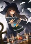 1girl ankh bangs black_cape black_headwear book brown_eyes brown_hair candle cape cardigan commentary_request eyebrows_behind_hair frilled_skirt frills green_skirt grey_cardigan hat heterochromia highres holding holding_book layered_skirt long_hair long_sleeves open_book original paper red_eyes skirt sleeves_past_wrists solo toka_(marchlizard) very_long_hair witch witch_hat