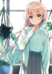 1girl ameshizuku_natsuki bangs black_skirt blurry blurry_foreground blush brown_hair closed_mouth clover commentary_request cowboy_shot eyebrows_visible_through_hair floating_hair flower four-leaf_clover green_eyes green_scarf green_sweater hand_up hanging_plant holding holding_flower indoors long_hair long_skirt long_sleeves looking_at_viewer original plant pleated_skirt potted_plant scarf scarf_removed signature skirt smile solo sweater sweater_tucked_in window