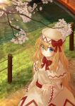 1girl absurdres blonde_hair blue_eyes bow bridge capelet cherry_blossoms commentary_request day dress ekaapetto expressionless eyes_visible_through_hair fairy_wings from_above grass hand_up hat hat_ribbon highres holding holding_petal lily_white long_hair long_sleeves looking_at_viewer looking_up open_hand outdoors petals red_bow red_neckwear ribbon road solo standing stream touhou tree_branch very_long_hair white_capelet white_dress white_headwear wide_sleeves wings