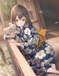 1girl absurdres animal animal_on_hand bangs barefoot blue_flower blue_kimono blurry blurry_background blush brown_hair closed_mouth commentary_request depth_of_field dutch_angle floral_print flower green_eyes hair_between_eyes hair_flower hair_ornament hairclip highres holding japanese_clothes kimono leaf leaves_in_wind long_hair nogi_momoko original outdoors print_kimono rabbit railing sash sitting smile solo x_hair_ornament