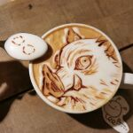 1boy boar_mask coffee coffee_mug cup food food_art hashibira_inosuke highres kimetsu_no_yaiba latte_art looking_at_viewer mug photo_(medium) portrait runapocket shadow solo spoon unconventional_media