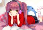 1girl black_shorts book eyebrows_visible_through_hair hands_on_own_face headphones heart_pillow hoodie lying open_book original penguin pillow pink_hair red_hoodie shorts socks