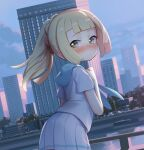 1girl bangs blonde_hair blunt_bangs blush building clenched_hand closed_mouth clouds commentary_request day fence floating_hair green_eyes hand_up lamppost leaning_forward lillie_(pokemon) long_hair looking_back outdoors pleated_skirt pokemon pokemon_(game) pokemon_sm ponytail shamonabe shiny shiny_hair shirt short_sleeves skirt sky solo water white_shirt white_skirt window