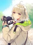 1girl ahoge amiya_(arknights) arknights beige_jacket blonde_hair camera commentary doctor_(arknights) dslr eyebrows_visible_through_hair facing_away hair_ornament highres holding holding_camera hood hood_down infection_monitor_(arknights) looking_at_viewer looking_back nanatsuka outdoors scene_(arknights) short_hair side_ponytail signature snowflake_hair_ornament solo upper_body wristband yellow_eyes