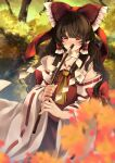 1girl ascot autumn_leaves blurry blurry_background blush bow brown_eyes brown_hair covering_mouth eyebrows_visible_through_hair frilled_shirt_collar frills gohei hair_between_eyes hair_bow hair_tubes hakurei_reimu highres long_hair looking_at_viewer meji_aniki nontraditional_miko red_bow red_skirt red_vest ribbon-trimmed_sleeves ribbon_trim skirt solo touhou vest wide_sleeves