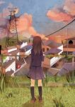 1girl black_legwear black_shirt black_skirt brown_hair cable car clouds cloudy_sky commentary_request fence from_behind grass ground_vehicle house kneehighs lamppost long_hair motor_vehicle original outdoors radio_tower scenery shirt skirt sky sunset tamagogayu1998 town